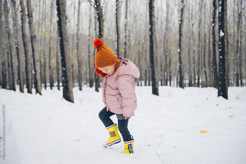 Toddle girl playing in a forest full of snow by Maa Hoo for Stocksy United