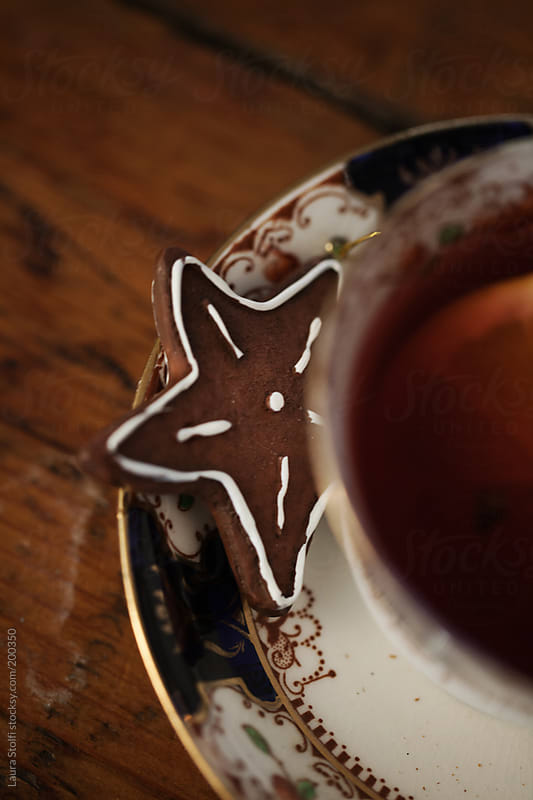 Close-up of star shaped christmas cookie close to vintage teacup by Laura Stolfi for Stocksy United