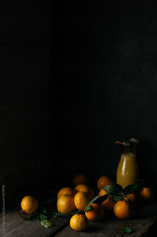 cluster of oranges and orange juice in kitchen by Levi Tijerina for Stocksy United