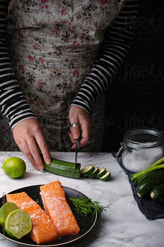 Woman preparing a salmon meal: Woman cutting courgette. by Darren Muir for Stocksy United