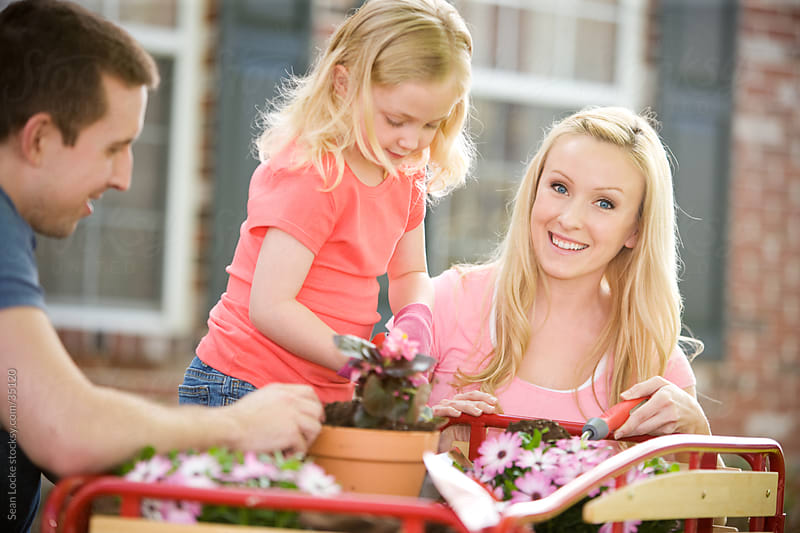 Planting: Cheerful Mother Outside with Family Doing Gardening by Sean Locke for Stocksy United