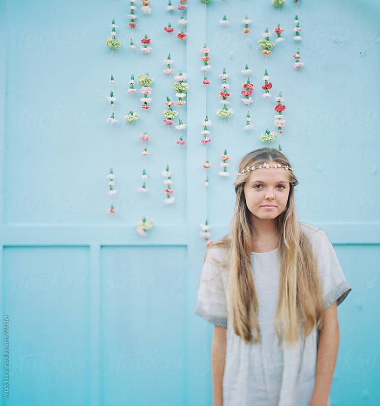 blonde girl against blue wall with hanging flowers by wendy laurel for Stocksy United