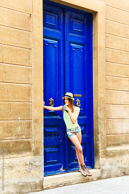 Young girl with cocktail with straw hat in front of blue door by BONNINSTUDIO for Stocksy United