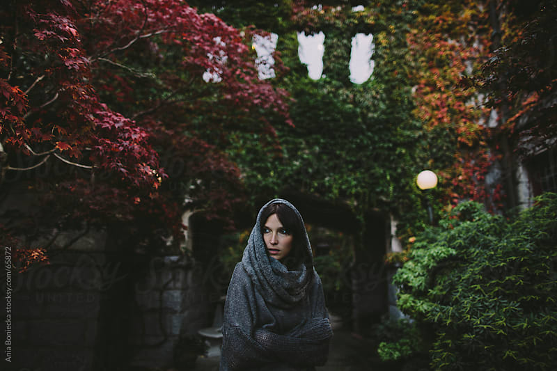 Beautiful woman in a shawl outdoors in the fall leaves by Ania Boniecka for Stocksy United