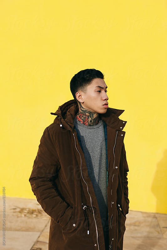 Portrait of an asian tattooed man standing in front of a yellow wall. by BONNINSTUDIO for Stocksy United
