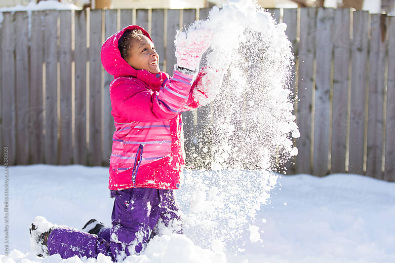 Tween girl throwing snow happily into the air by anya brewley schultheiss for Stocksy United