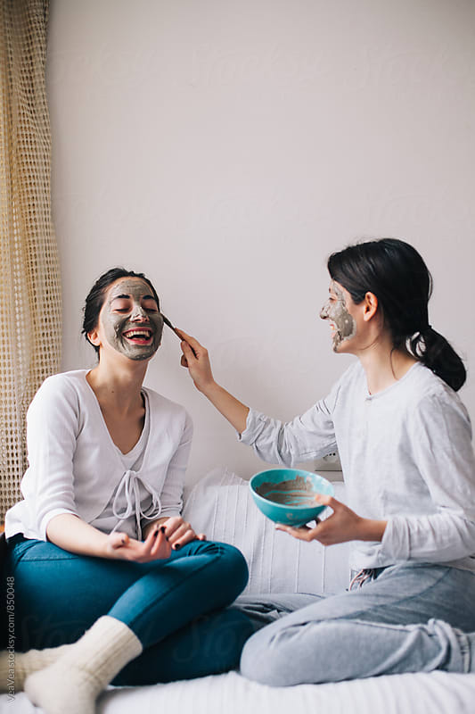 Two female friends having beauty treatment in their home  by VeaVea for Stocksy United