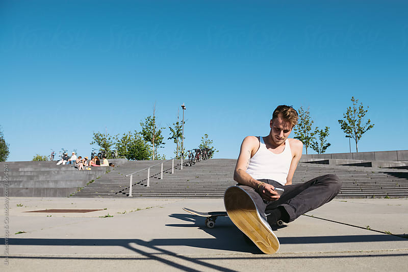 Skater with smart phone resting by Urs Siedentop & Co for Stocksy United
