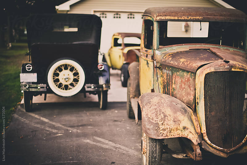 three vintage, rusty automobiles in front of garage by Lisa MacIntosh for Stocksy United