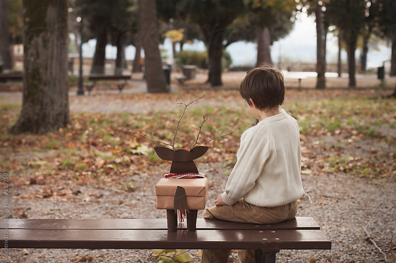 Boy sitting with a hand made gift box in the park by Beatrix Boros for Stocksy United