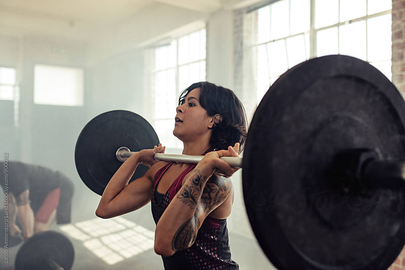 Woman doing front squats with barbells  by Jacob Lund for Stocksy United