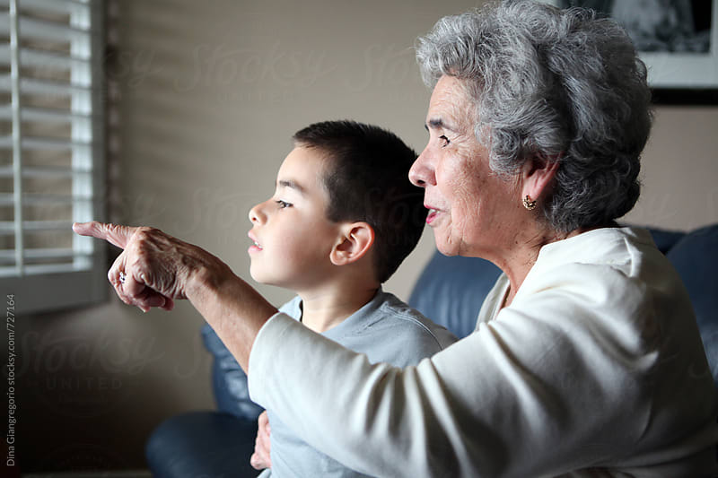 Hispanic Grandma With Grandson Pointing Out the Window by Dina Giangregorio for Stocksy United