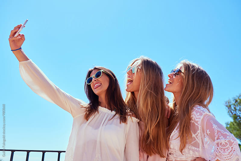 Three friends taking selfie against of blue sky by Guille Faingold for Stocksy United