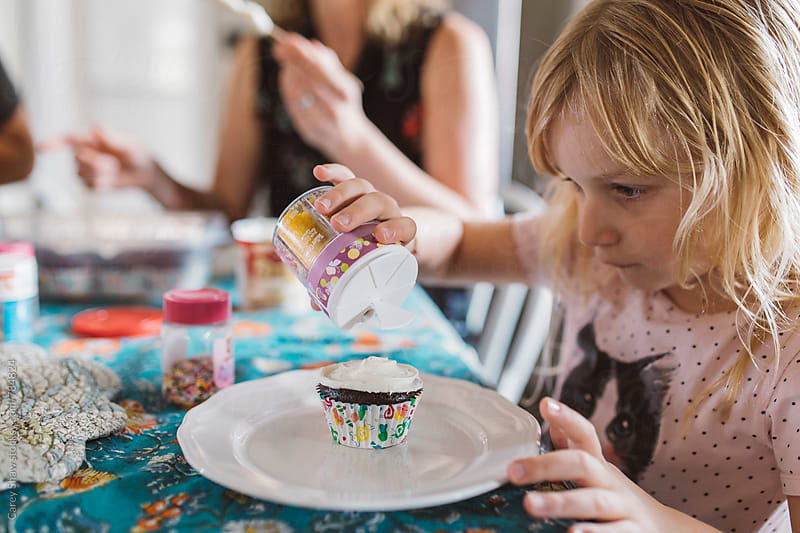 Young girl decorating cupcakes by Carey Shaw for Stocksy United