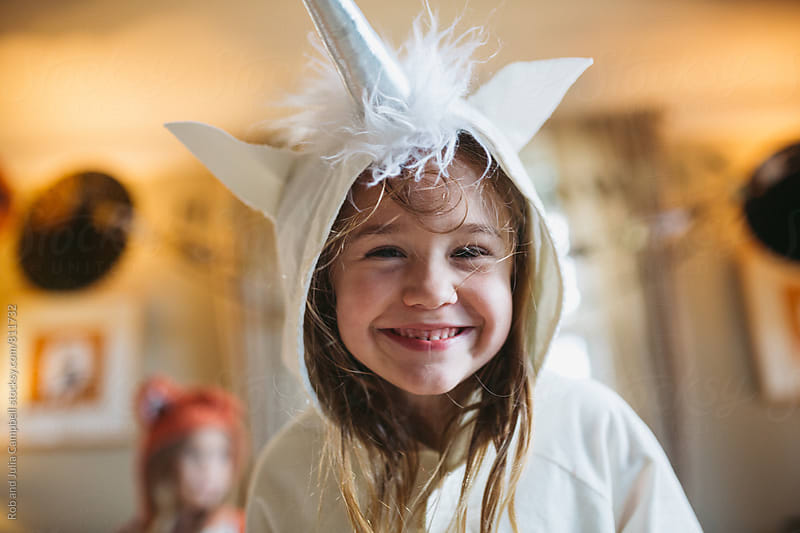 Girl in unicorn costume staring at camera smiling by Rob and Julia Campbell for Stocksy United