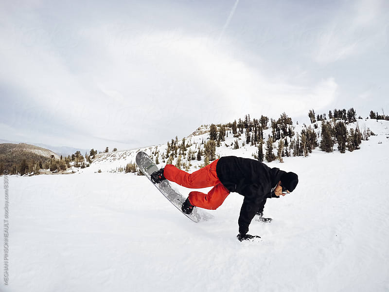 Male Snowboarder Does Nose Slide on Ski Slope by MEGHAN PINSONNEAULT for Stocksy United