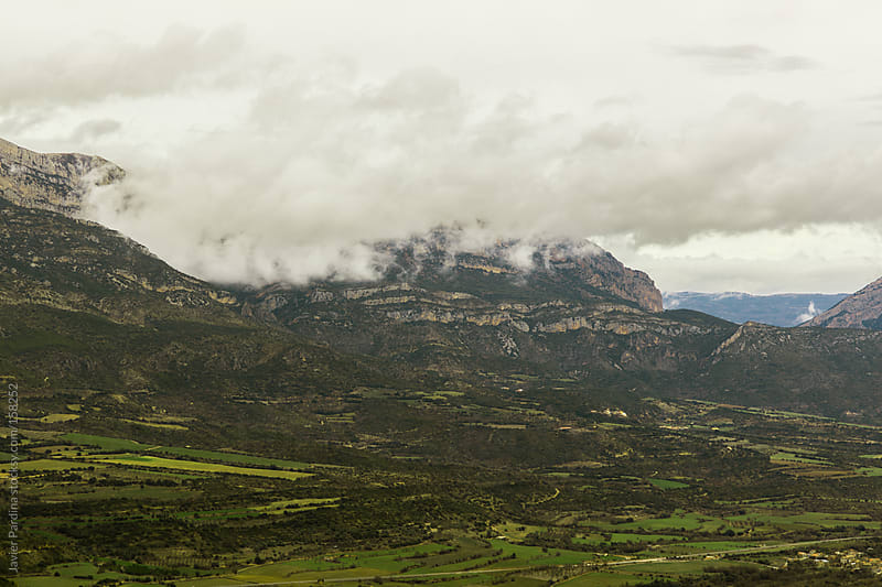landscape with mountains and cloudy sky by Javier Pardina for Stocksy United