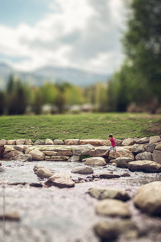 Boy jumping boulders in a mountain river in summer by Angela Lumsden for Stocksy United