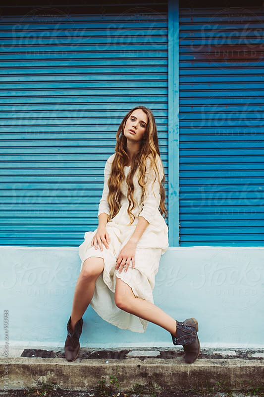 Beautiful Bohemian Woman in front of Blue Garage Door by Marija Savic for Stocksy United