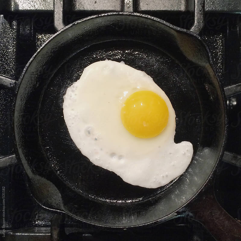 Looking down at a egg frying in a cast iron pan. by Lucas Saugen for Stocksy United