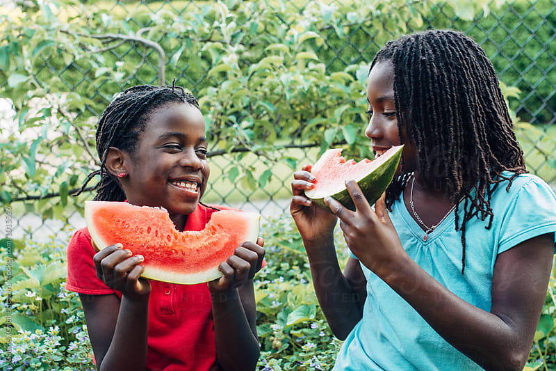 African American girls eating watermelon and smiling by Gabriel (Gabi) Bucataru for Stocksy United