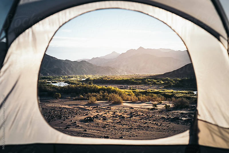 View from with a tent over a rugged desert landscape and river at sunset by Micky Wiswedel for Stocksy United