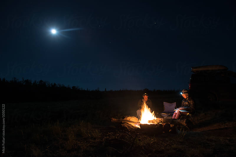 Couple reading by campfire with full moon by Mick Follari for Stocksy United