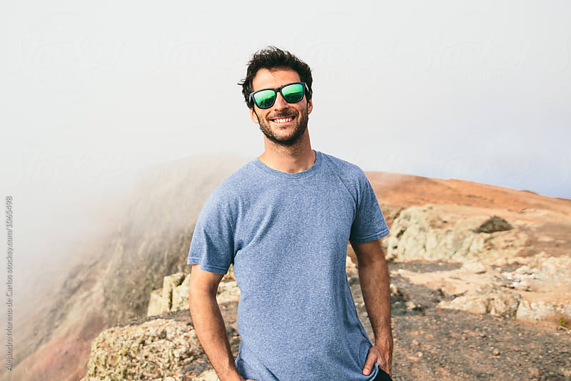 Portrait of cheerful man in mirrrored sunglasses against of rocky land in fog by Alejandro Moreno de Carlos for Stocksy United