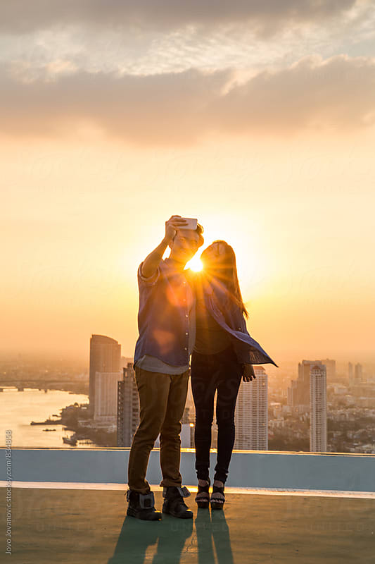 Couple pose for a rooftop selfie by Jovo Jovanovic for Stocksy United