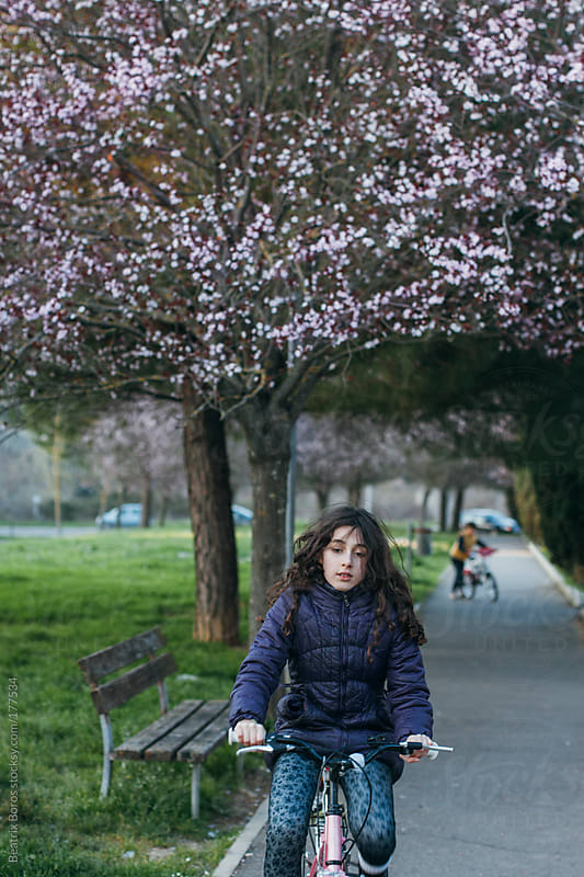 Girl riding a bike in a park in Spring by Beatrix Boros for Stocksy United