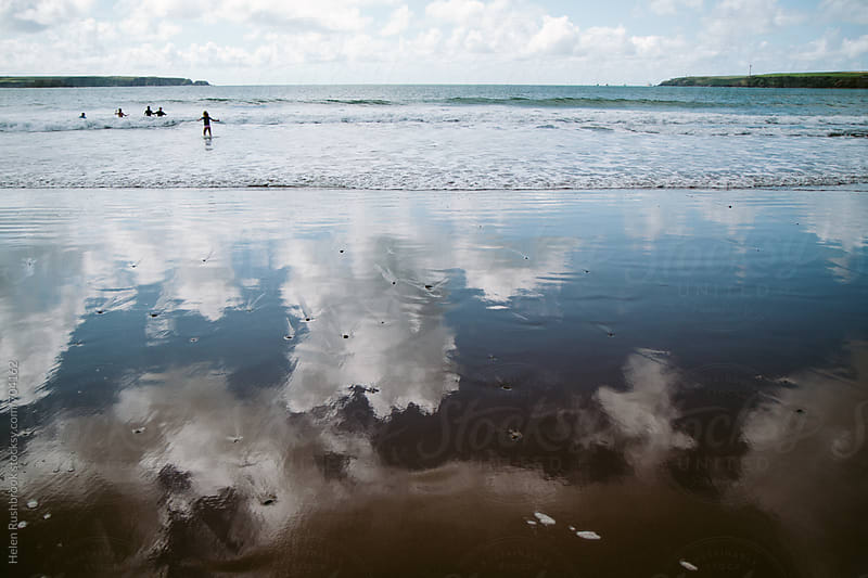Clouds reflected in standing water on a beach. In the background, small people. by Helen Rushbrook for Stocksy United