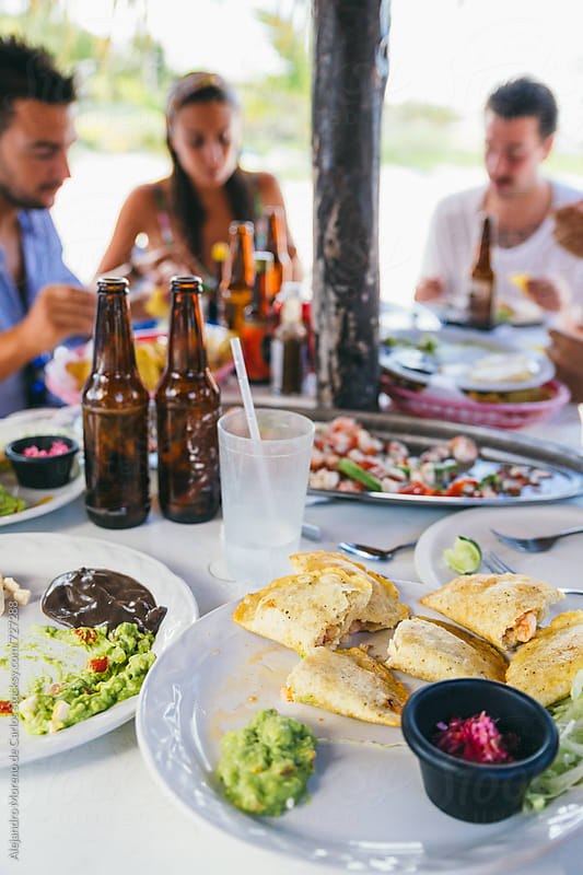 Group of friends enjoying Mexican food in a beach bar by Alejandro Moreno de Carlos for Stocksy United