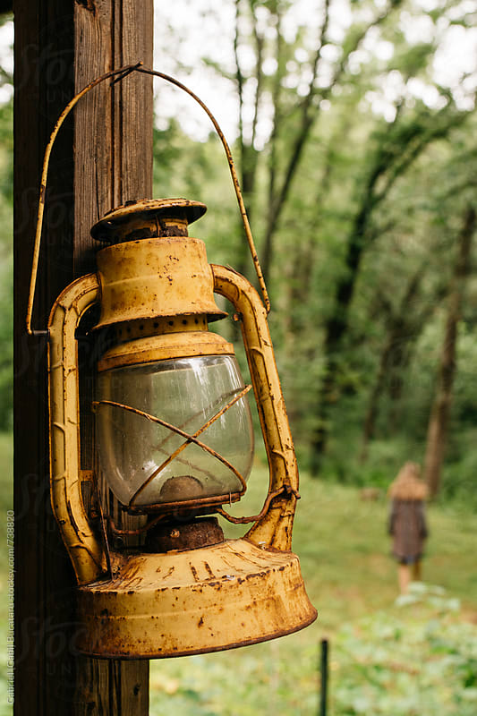 Yellow lantern with woman walking in a forest in background by Gabriel (Gabi) Bucataru for Stocksy United