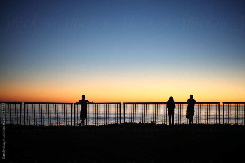 Three silhouettes watching the sunset in Santa Cruz by Carolyn Lagattuta for Stocksy United