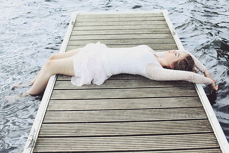 Sleeping on the jetty by Kitty Gallannaugh for Stocksy United