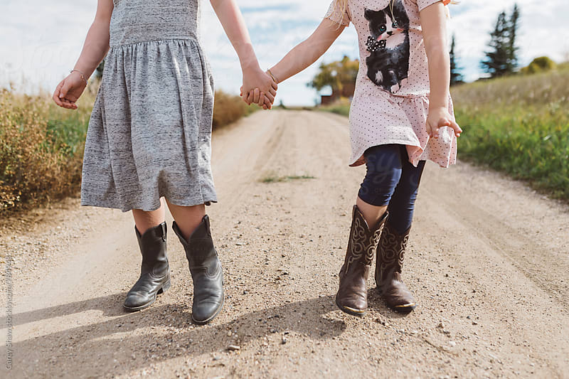 Young sisters wearing cowboy boots and holding hands by Carey Shaw for Stocksy United