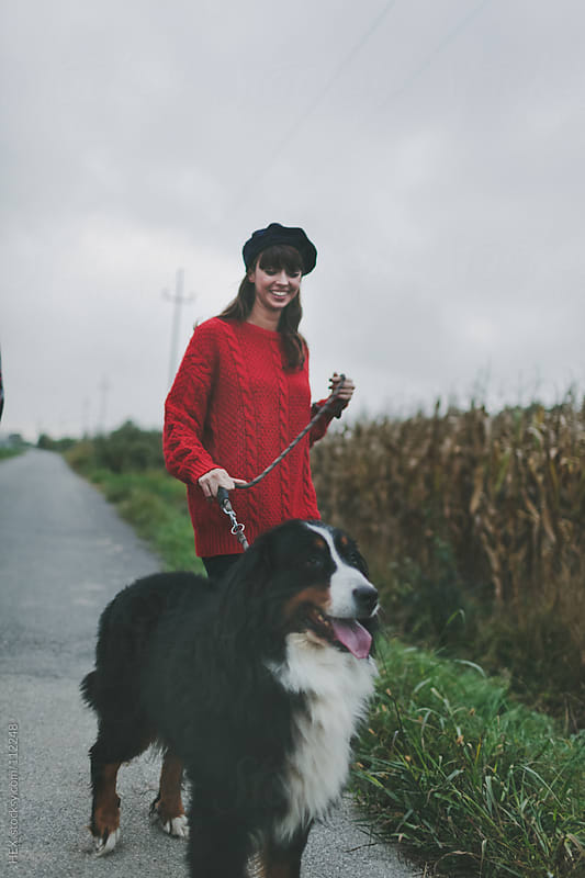 Young Woman Walking with Big Dog by HEX. for Stocksy United