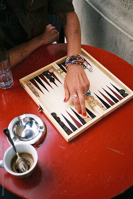 A young girl playing backgammon by Aleksandra Martinovic for Stocksy United