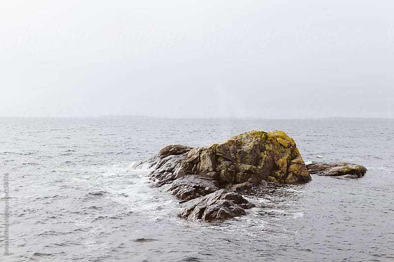 Small island in the foggy sea with steel gray waves by Jonas Räfling for Stocksy United