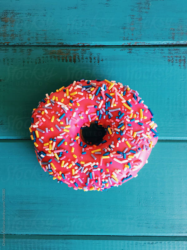 A pink donut with sprinkles by Chelsea Victoria for Stocksy United