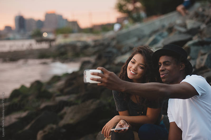 Couple taking a selfie  by Lauren Naefe for Stocksy United