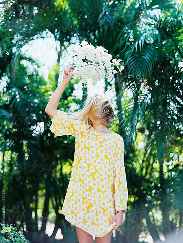 blonde girl shaking her hair with white flowers held high by wendy laurel for Stocksy United