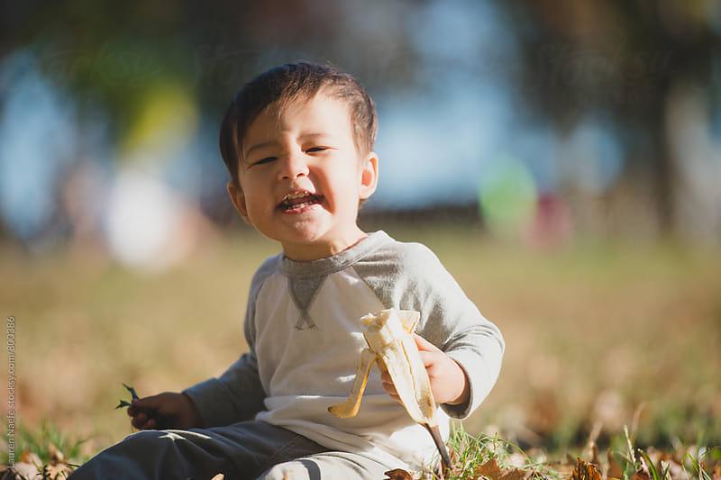 Happy kid eating banana by Lauren Naefe for Stocksy United
