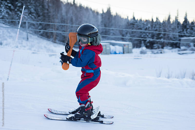 young child on skis going up via tow rope by Tara Romasanta for Stocksy United