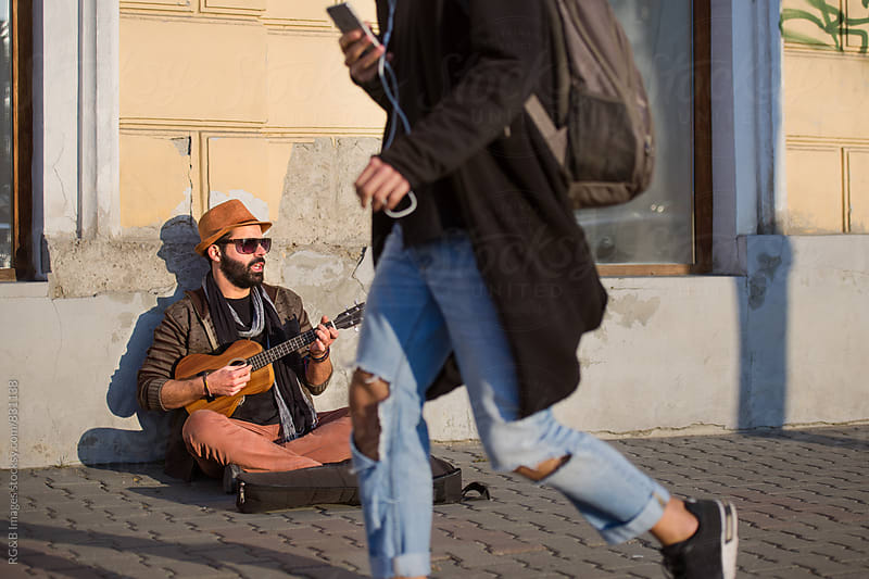 Street musician sitting on the sidewalk playing ukulele by RG&B Images for Stocksy United