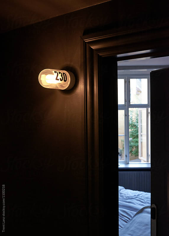 Lamp with room number and open door by Trent Lanz for Stocksy United