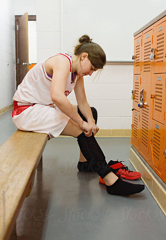 female basketball player puts knee pads on in locker room by Tana Teel for Stocksy United