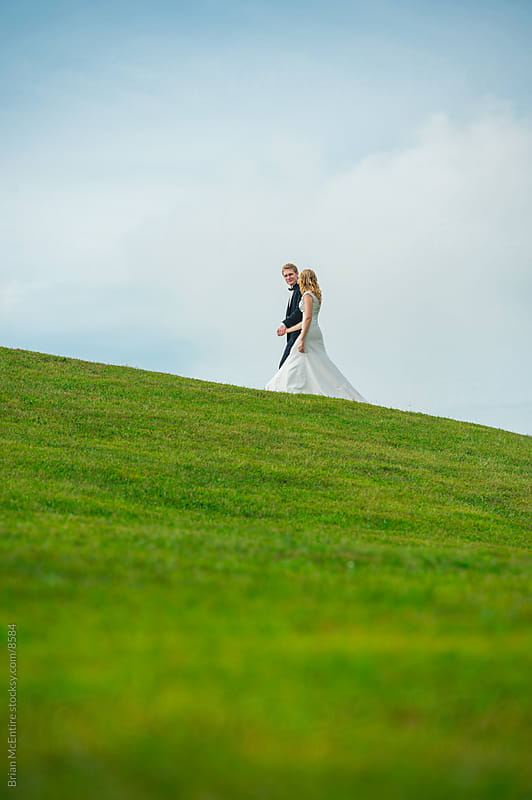 Bride and Groom Walking along Lush Hill Side by Brian McEntire for Stocksy United