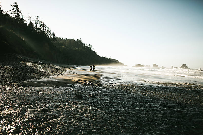 Surfers in the Distance Walking the Oregon Coast by Kristine Weilert for Stocksy United