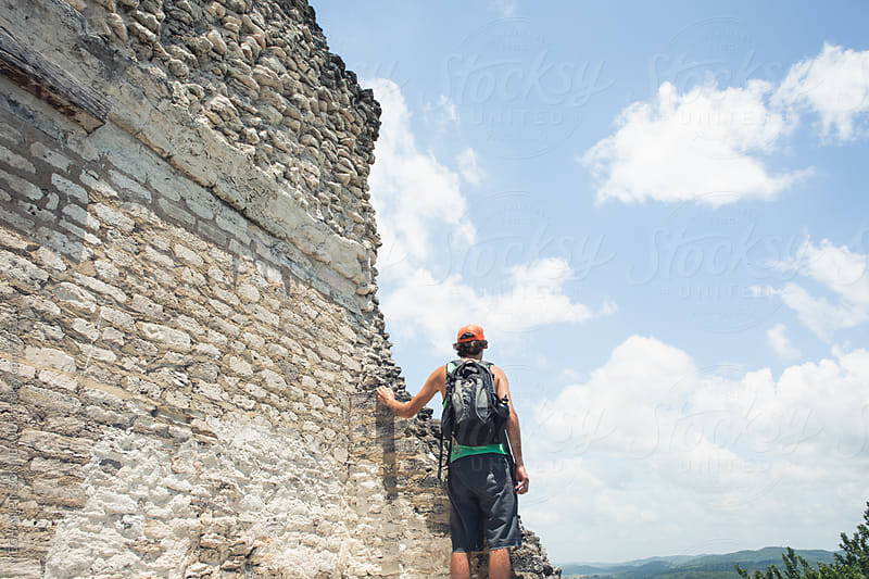 Man on Top of Ancient Mayan Temple  by MEGHAN PINSONNEAULT for Stocksy United